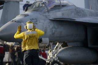 Sailor directs an F/A-18F Super Hornet on the flight deck of USS Harry S. Truman.