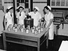 State High School, Domestic Science, Fruit Preserving - Brisbane (Queensland State Archives) Tags: girls students cooking classroom teaching kitchen education secondary domesticscience statehighschool brisbane queensland history archives qld queenslandstatearchives uniform apron jars glass pot tie hat
