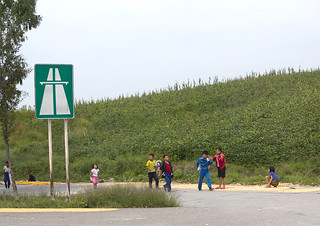 North Korean children playing in front of a highway entrance road sign near the Demilitarized Zone, North Hwanghae Province, Panmunjom, North Korea