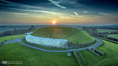 Sunset over Sídh an Bhrogha (mythicalireland) Tags: newgrange monument sunset setting sun dusk evening sky clouds contrails grass landscape boyne valley ancient prehistoric stone age neolithic megalithic drone aerial dji phantom 3 advanced