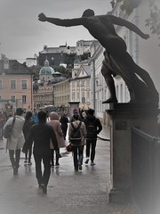 Don't go away! (SM Tham) Tags: europe austria salzburg mirabell palace gardens entrance exit statue pedestal people cityscape buildings dom cathedral hohensalzburg fortress castle wet puddles street road