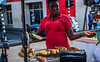 2017 - Regent Cruise - Grenada - Pay First, Please (Ted's photos - For Me & You) Tags: 2017 cropped grenada nikon nikond750 nikonfx regentcruise stgeorge's tedmcgrath tedsphotos vignetting grill bbq corn food streetscene street female umbrellas red redrule tongs handout ears cornears teeth dents candid portrait face