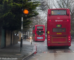 A Wet Day In Leyton 4 (M C Smith) Tags: bus buses red leyton pentax kp lights crossing orange black white pavement kerb umbrella gates green fence wall letters numbers symbols branches sky grey blue lines yellow parking junction people walking poster