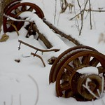 An antique axle resting in the cold embrace of winter's snow. thumbnail