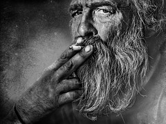 Old smoker (Ales Dusa) Tags: man outdoor face beard cigarette smoker old elderly beardedman bw blackandwhite alesdusa strongcontrast wrinkles oldwrinkledman canon5dm2 ef70300mmf456lisusm streetportrait streetshot portrait dramaticportrait closeup human humanity texture strongcharacter poverty people candidlight powerfulface monochrome charismaticman hand fingers cigarettebetweenfingers candideyetoeye greaterphotographers