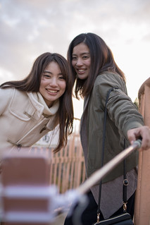 Young sisters taking selfie picture together at observatory