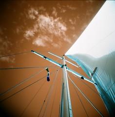 up, on the sailboat Taipan (.grux.) Tags: holga120n film lomography lomachrome turquoisexr100400 120 mediumformat 6x6 plasticfantastic zonefocus sailboat up sail sky clouds pacific banderasbay puertovallarta mexico