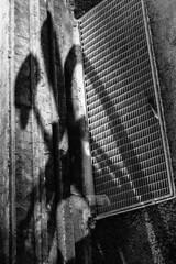 Deviant Bike (Thomas Listl) Tags: thomaslistl blackandwhite biancoenegro noiretblanc bike bicycle shadow light contrast grid shaft manhole graphical abstract vsco 50mm