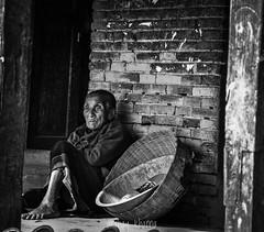 An old woman overlooking Pottery Square in Bhaktapur, Nepal. (akshaykhanna) Tags: people 18105mm blackandwhite nikonphoto nikond3100 nikon travel potterysquare bhaktapur nepal