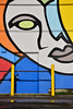 I'll be watching you (James_D_Images) Tags: wall mural art painting back door face eye colourful blue yellow gray black red orange posts railing lock alley asphalt cement vancouver britishcolumbia frontlit bright shadow