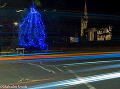 Christmas Light Trails (M C Smith) Tags: pentax k3 christmas tree lights blue red church spire road lighttrails chingford posters hedge wall green grass lines posts yellow white