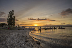 Great day for it (zebedee1971) Tags: lake sunrise taupo fishing trout volcano crater new zealand boats pier wharf wooden structure shore shoreline sand stones sky sun sunlight clouds high trees beach