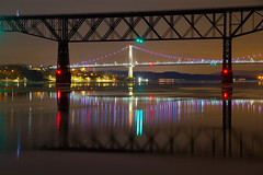 Two Bridges on a Winter Night (SunnyDazzled) Tags: poughkeepsie newyork hudson river historic cantilever bridge walkway pedestrian railroad fdr midhudson suspension reflection night ice winter chill cold colorful longexposure train citylights