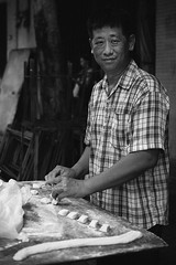 Man Cutting Dough Into Pieces (Thailand) (tetzuOzawa) Tags: man stall bw blackandwhite bangkok thailand asia