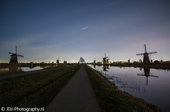 Silent night (JdJ Photography (www.jdj-photography.nl)) Tags: kinderdijk molenwaard alblasserwaard zuidholland nederland netherlands europa europe avond evening molens windmills voetpad footpath fietspad cyclingpath boom tree sloot ditch reflectie reflection brug bridge lucht sky sterren stars
