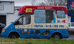 Mister Whippy (M C Smith) Tags: icecream van blue yellow red green pentax kp letters numbers symbols white orange road buildings poster advertising rain wet silver black cars parked trees sky grey phoneline