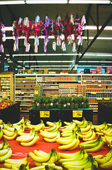 colors in a market (janette_j) Tags: bananas pinatas cooler 35 mm film ikon n65