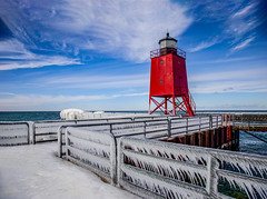 Icy Pier on the Lake (T P Mann Photography) Tags: canon red charlevoix sunlit sun seascape sea water michigan hff friday fence railings clouds sky blue frozen icicles lighthouse winter cold ice pier ngc