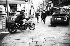 Suzuki rider, Amemura (Eric Flexyourhead) Tags: amerikamura amemura アメリカ村 chuo chuoku 中央区 osaka osakashi 大阪市 kansai 関西地方 japan 日本 city urban street streetscape streetscene streetphotography bike motorbike motorcycle japanese suzuki biker movement motion blur pan panning monochrome blackwhite bw ricohgr