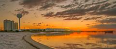 Evening Golden Reflections (Stuart Schaefer Photography) Tags: glow goldenhour building sunset water reflections outdoor sonya9 evening florida sun watertower sony travel sonyalpha seascape navarrebeach cloudscape boat landscape clouds bay dusk sky skyline