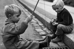Fishing (theirhistory) Tags: boys children kids street road grate drain gutter rod line fish jacket dungarees jumper wellies trousers wellingtons