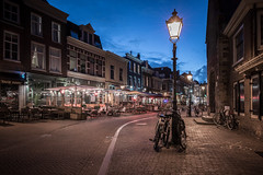 Take Away (McQuaide Photography) Tags: haarlem noordholland northholland netherlands nederland holland dutch europe sony a7rii ilce7rm2 alpha mirrorless 1635mm sonyzeiss zeiss variotessar fullframe mcquaidephotography lightroom adobe photoshop tripod manfrotto stad city urban lowlight architecture outdoor outside illuminated street straat oudegroenmarkt wideangle wideanglelens groothoek building longexposure oldstreet old oud character traditional authentic atmosphere sfeer light licht bike bicycle fiets streetlight lantaarnpaal lamppost bluehour dusk twilight takeaway restaurant terrace nopeople
