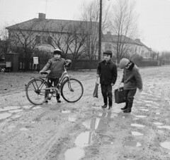Is it too wet for school? (theirhistory) Tags: children boys kids street road flood puddle bike bicycle hat jacket trousers wellies satchel case boots