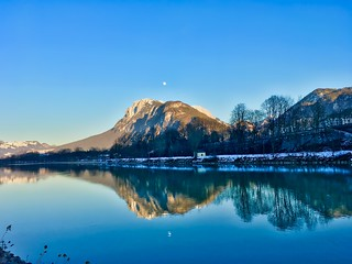 The moon over Zahmer Kaiser mountain in the Alps by the river Inn on a cold and clear winter morning