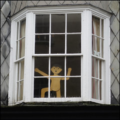 cheerful (but a bit two-dimensional) (Philip Watson) Tags: lymeregis dorset seaside bleak baywindow figure person boy cutout