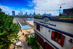 Panama City, Panama, from Casco Viejo (` Toshio ') Tags: toshio panamacity panama cascoviejo oldtown bay city skyline centralamerica cafe buildings architecture travel table bistro shoreline ocean panamabay gulfofpanama