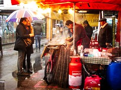 Warm and Dry (garryknight) Tags: panasonic lumix dmctz70 on1photoraw2018 london creativecommons ccby30 bricklane market stall food customer rain umbrella stallholder