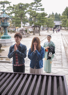Japanese people praying in front of temple mail hall
