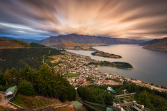 Queenstown Skyline (Scintt) Tags: newzealand landscape urban cityscape nature natural sun sky glow orange golden yellow dramatic surreal cloud telephoto water lake pond clouds town city buildings skyline trees travel tourism queenstown park mountains hills rural scintt scintillation jonchiangphotography exploration summer wakatipu sunset twilight evening dusk range forest woods wideangle haida longexposure slowshutter neutraldensity filter cablecar