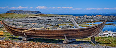 A small Norse boat (Brett of Binnshire) Tags: shoreline lanseauxmeadows bay weather clouds historicalsite ocean water iceberg manipulations scenic museum locationrecorded canada cove boat 2391 newfoundland