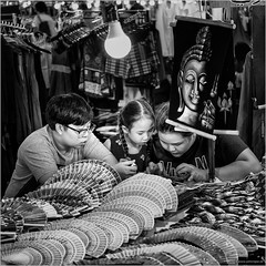 Play the game (John Riper) Tags: johnriper street photography straatfotografie square vierkant bw black white zwartwit mono monochrome chiangmai thailand streetfood candid john riper xt2 fujifilm xf35 mm f2 kids smart phone playing game shop stall market lamp fans painting