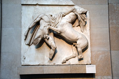 DSC_9606 The British Museum London The Parthenon Sculptures. The Lapith lunges at the centaur with his left hand while preparing to strike with his right. The heads of both figures are in Athens. South Metope VII (photographer695) Tags: the british museum london lapith lunges centaur with his left hand while preparing strike right heads both figures athens south metope vii parthenon sculptures
