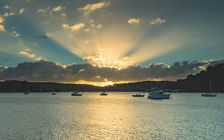 Sunrise Waterscape with Boats and Sun Rays