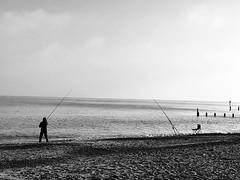 Optometrist (martynchadwick) Tags: optometrist hopeful edge land wet waves water sea sand cast tide bait shore man rods silhouette white black coast coastal seaside beach fisherman fishing