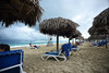 Threat of Rain (Poocher7) Tags: beach footprintsinthesand water ocean gulfofmexico thatchedroof shelters sand lifeguardplatform loungechairs bluetowels relaxation peaceful waves cloudy raincoming threateningtorain people varadero cuba carribean