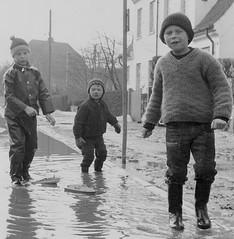 Playing in the floods (theirhistory) Tags: children boys kids jumper trousers street wellies road water puddle playing rubberboots hat waterproof jacket ship boat liner