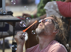 Forever blowing bubbles! (albertusmagnus) Tags: subduedstringbandjamboree candidportrait streetphotography candidstreetportrait relaxing simplethings bubbles blowingbubbles adultmanblowingbubbles albertusmagnus nikond5000 nikkor70300mmlens naturallight summer maleportrait graybeard glasses