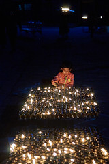 Tibetan girl lighting buddhist candles, Boudhanath, Kathmandu, Nepal (Alex_Saurel) Tags: portrait silhouettes portraiture portray halfbody asie culture 35mmprint pavés scans candles asian littlegirl candle work petitefille motif pattern bouddhisme buddhism people dark khāsacaitya tibetangirl boudhanath lightingcandles asia oillamp tibétaine streetscene khāsti cobblestones travel sanctuairebouddhiste lifescene बौद्धनाथ imagetype buddhistsanctuary photospecs photoreport jarungkhashor photoreportage reportage kathmandu nuit bouddhanath night bodnath byarungkhashor photojournalism main religion stockcategories hand bougies plantaille traditional time katmandou tradition nepal scènedevie lifestyles sony50mmf14sal50f14