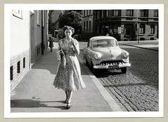 """Opel Olympia Rekord (Vintage Cars & People) Tags: vintage classic black white """"blackwhite"""" sw photo foto photography automobile car cars motor opel olympia rekord opelrekord opelolympiarekord economicmiracle wirtschaftswunder 1950s fifties vehicle antique auto woman lady dress summerdress floraldress cardigan cobbles citystreet"""