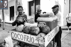A coconut vendor sets one for a customer (House_of_M) Tags: colombia cartagena street streetphotography