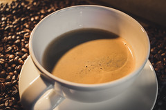 A cup of coffee with coffee beans in background (janiskikans_photography) Tags: coffee cup brown espresso cafe caffeine black closeup drink breakfast aroma morning bean beverage grain tasty smoke mug latte roasted taste fresh background foam close dark aromatic porcelain hot arabic bio seed organic java isolated cafeteria roast liquid freshness beans roaster white coffeebreak coffeebean life arabica warm food coffeecup