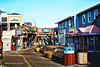 Pier 39 on San Francisco Bay (garofano_richard) Tags: pier waterfront buildings planks signs flowers streetlamps walkways railings outdoorchairs stores resturants recyclebins stairs skyline california sanfranciscobay touristattractions