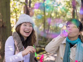 Happy Japanese sisters playing with bubbles in forest