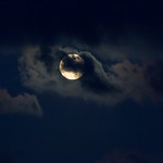 Full moon partially covered by clouds thumbnail