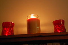 Candles On A Bookshelf. (dccradio) Tags: lumberton nc northcarolina robesoncounty indoors inside candle candles burning illuminated flame redcandleholder candleholder tealightcandle jarcandle wall fire nikon d40 dslr tealight red light candlelight