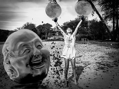 Juggling Moons (Mildred Alpern) Tags: girl moons face outdoors hands leaves trees monochrome blackwhite